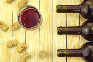 Glass of wine on background of bottles and corks