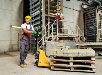 Young worker moving paving stones with pallet truck on a factory