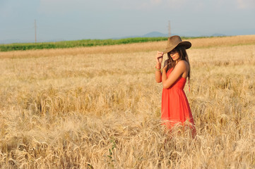 Beautiful woman with orange dress and hat on field