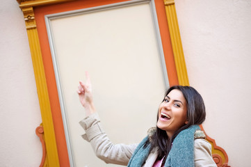Young cheerful woman smiling showing to a wall frame