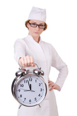 Attractive woman doctor with big clock  isolated on white