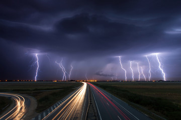 Tempete Thunderstorm and lightnings in night over a highway with car lig