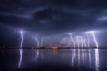 Fotobehang Onweer Thunderstorm and lightnings in night over a lake with reflaction
