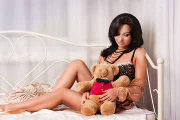 beautiful woman sitting on bed with bear