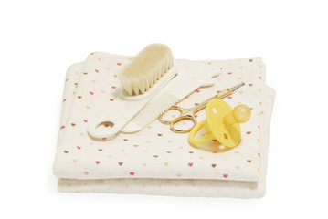 Diapers, nail scissors, combs and nipple on white background