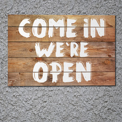 "Vintage ""Come in we`re open"" wooden sign on stucco concrete wall"
