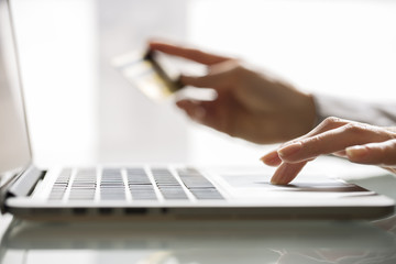 Woman shopping using laptop and credit card .indoor.close-up