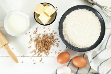 farina uova burro e latte su tavolo bianco