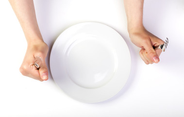 Female Hands holding Fork and Knife next to an Empty Plate