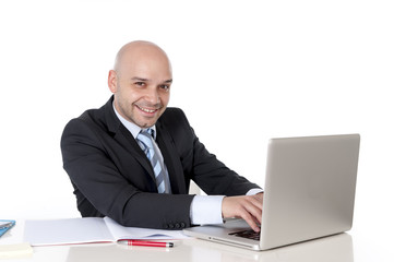 bald happy latin business man working on laptop smiling camera