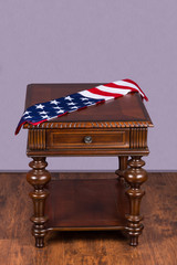 Wooden table with american flag on hardwood floor