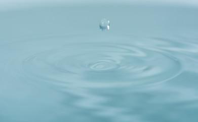 Water drop falling into water