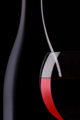 Wineglass of red wine and a bottle