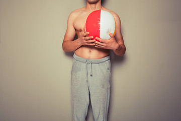 Athletic young man with a beach ball