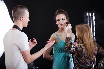 Phototograper, make-up artist and model working together