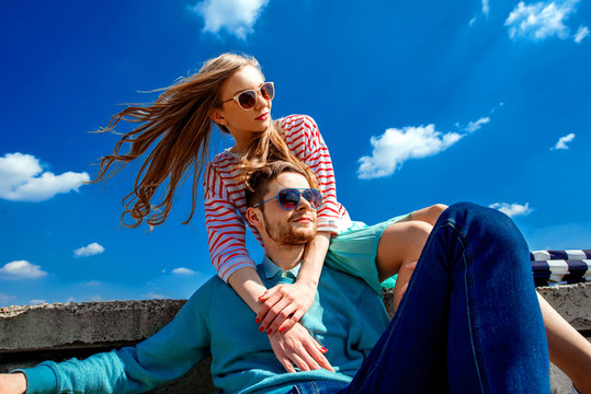 Smiling couple sitting on the roof embracing and smiling on the