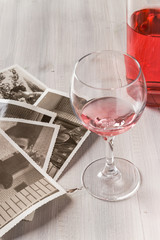 Memories. Bottle of rose wine, wine glass and old photos