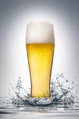Glass of beer with water splash.