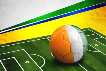 Soccer ball with Cote D'Ivore flag on pitch