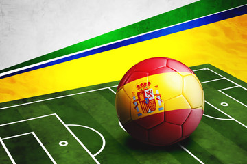 Soccer ball with Spain flag on pitch