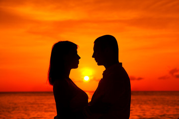 Romantic couple kissing at tropical beach with sunset in the bac