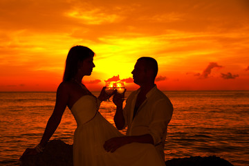 Romantic couple at tropical beach with sunset in the background