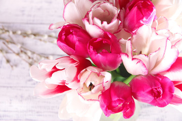 Beautiful tulips in glass jug on light background