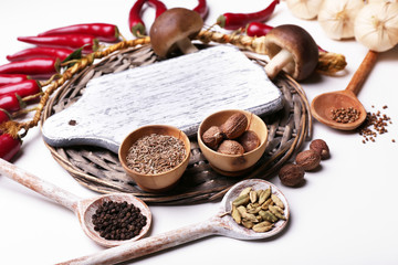 Different spices with blank cutting board, isolated on white