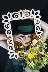 Woman with red hair wearing a top hat posing with picture frame