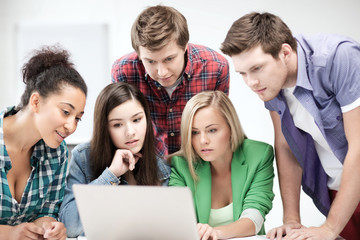 international students looking at laptop at school