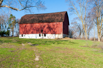 A weathered red barn on a hill