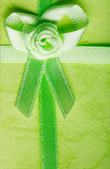 Giftbox closeup. Ribbon with bow on green background