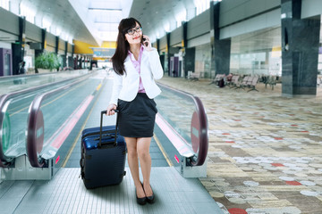 Busy businesswoman on escalator