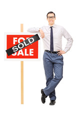 Male real estate agent leaning on a sold sign