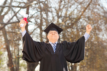 Mature graduate gesturing happiness outdoors