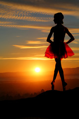 Young ballerina on a mountain overlooking a beautiful sunset