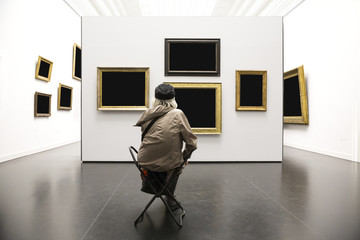 old lady sits in front of wall with paintings in art gallery