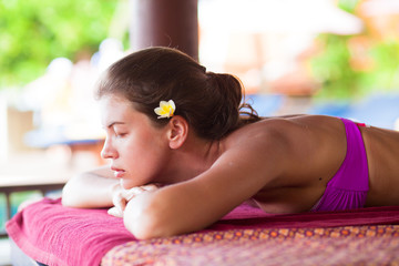 beautiful young woman with flower in hair lying in spa