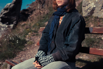 Woman relaxing on a bench in the mountains