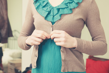 Young woman buttoning her blouse