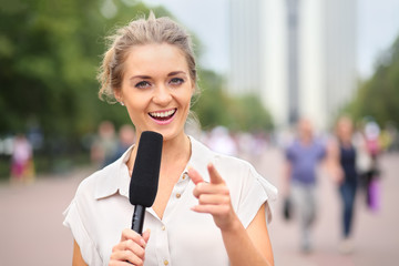 A smiling girl reporter with microphone in hand