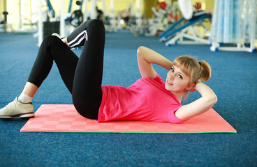 Young woman doing stretching exercise in the gym