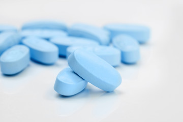 Bunch of blue pills on grey table