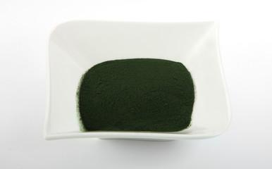 Spirulina powder in bowl on bright background