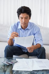 Man sitting on couch working out his finances