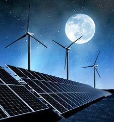 solar energy panels and wind turbines in night