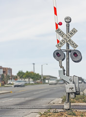 Railroad crossing sign on urban street with traffic