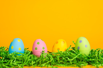 4 assorted color Easter eggs on a bright yellow background