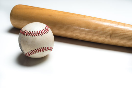 Wooden baseball bat and ball on white