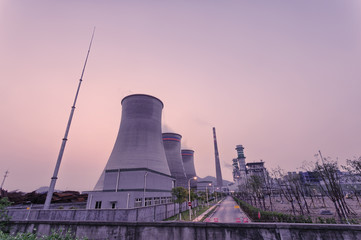 coal fired power station with cooling towers releasing steam int